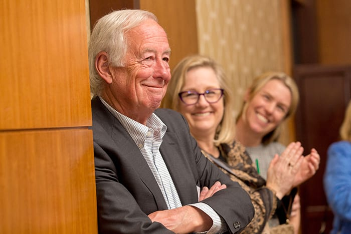 Bob Hill leans against a wall while smiling, he is a bold investor.