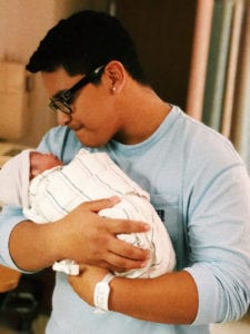 Photo of Marvin holding his newborn son, Matthew.
