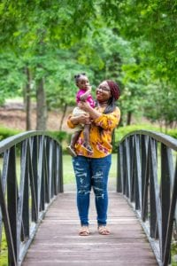 Terri and Aubrielle standing on a bridge in the park.